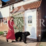 Lady with dog walking by White uPVC door